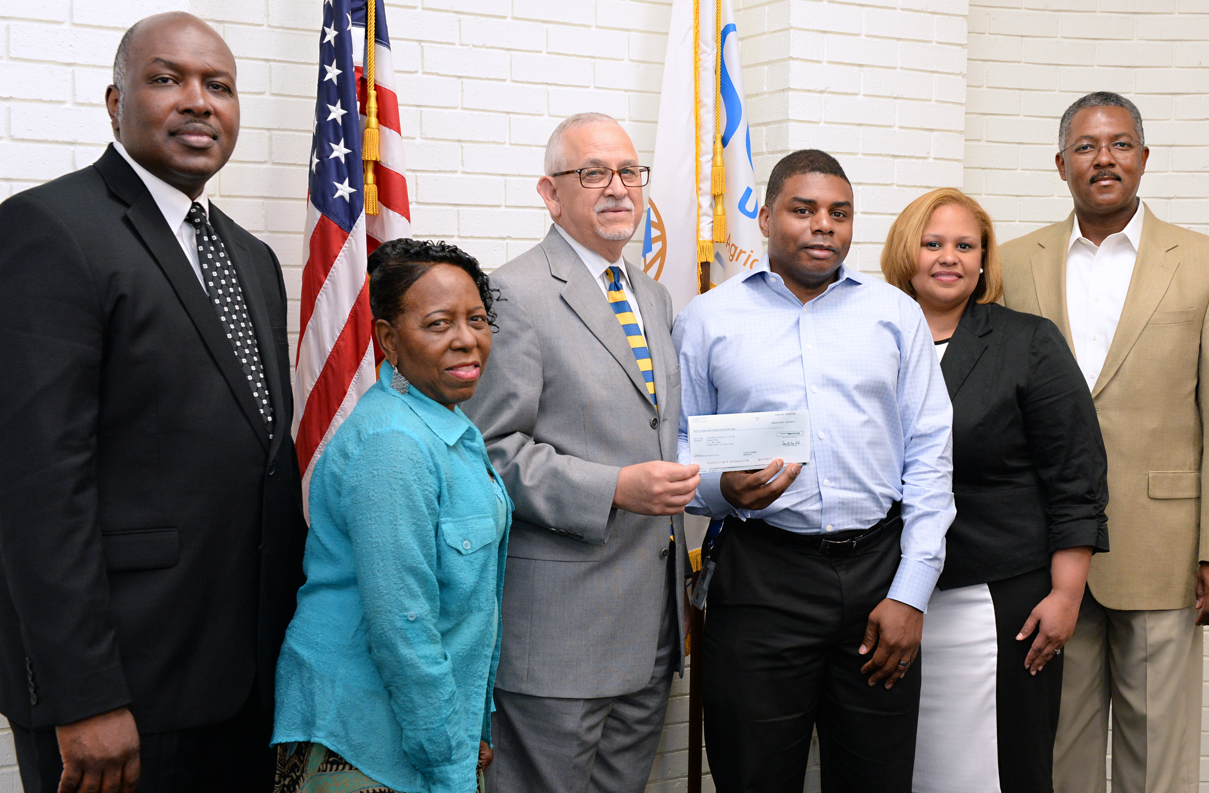 The ExxonMobil check presentation included from left, ExxonMobil's Wilbert Ferdinand, SU College of Engineering representative Janifer Peters, SUBR Chancellor Dr. James L. Llorens, Shabaka Gibson, and Claudette Bradford, both with ExxonMobil, and Phil Smith, with the SU Foundation.
